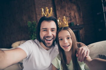 Closeup photo of little funny lady her handsome daddy friendship sit comfy sofa making taking selfies hugging wear golden crowns celebrities famous person house room indoors