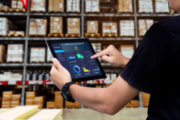 Smart warehouse management system.Worker hands holding tablet on blurred warehouse as background Wall mural