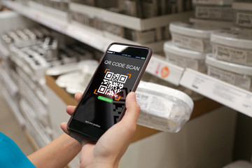 Smart retail concept.Woman scanning QR code for product details in supermarket with mobile phone