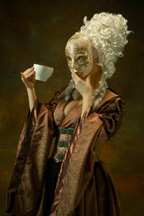 Drinking coffee with mask. Portrait of medieval young woman in brown vintage clothing on dark background. Female model as a duchess, royal person. Concept of comparison of eras, modern, fashion