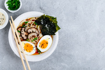 Asian Vegetarian Udon or Ramen noodles soup in bowl with Shiitake mushrooms, boiled eggs and nori sheets
