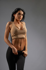 Stylish brunette female model showing abs.