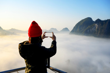 woman taking photo of beautiful morning fog above the mountain