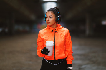 Young woman in orange hoodie under overpasses resting after jogging in cold weather holding protein shake and listens to music through headphones