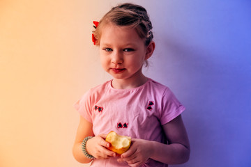 portrait of a little girl eating apple