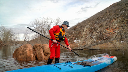 Senior male stand up paddler in a dry suit