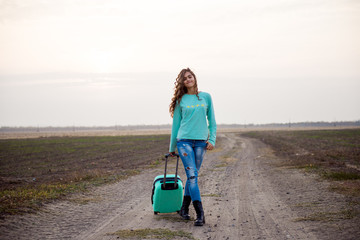 girl with suitcase on the road. girl with a suitcase is walking along a rural road.  girl with wavy hair returns home. Young woman with a suitcase. Student travel, girl in jeans and with a suitcase