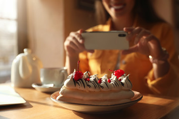 Young blogger taking picture of dessert at table in cafe, focus on plate