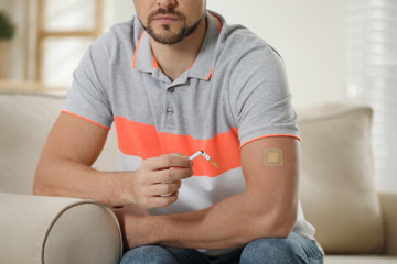 Man with nicotine patch and cigarette at home, closeup