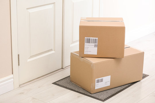 Parcels on rug near door. Delivery service