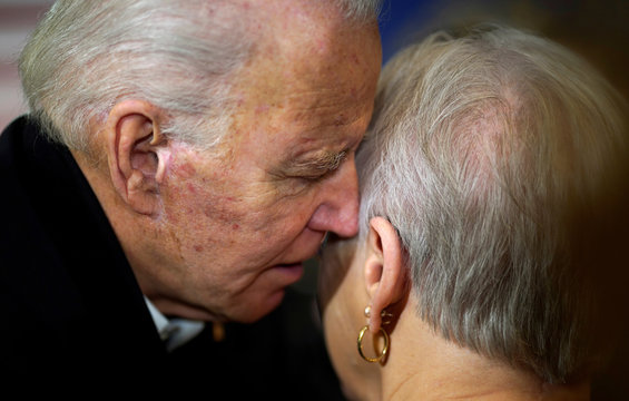 Democratic presidential candidate and former Vice President Joe Biden whispers in the ear of a supporter after a campaign event in Somersworth