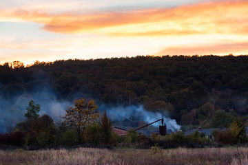 Rural background with countryside nature and houses in autumn evening