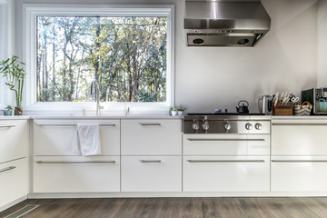 spacious large modern white kitchen recently updated with high end appliannces, wood floors, picture windows, white cabinets and wood beams and a great view of the backyard