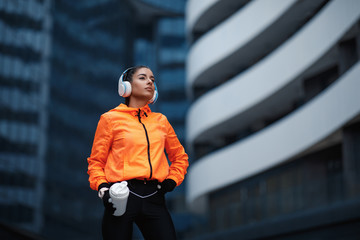 Young woman in orange hoodie resting after jogging in cold weather holding protein shake and listens to music through headphones