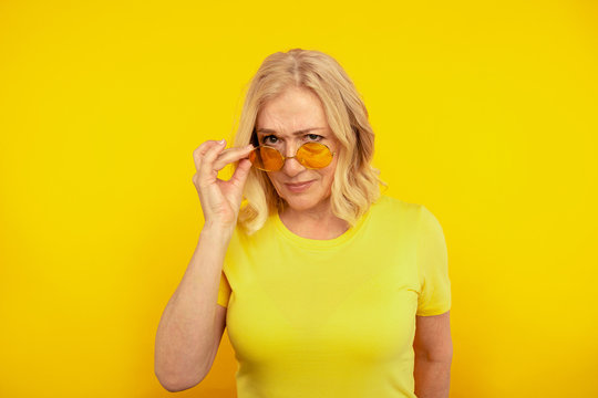 Portrait of serious female in sunglasses in the yellow studio