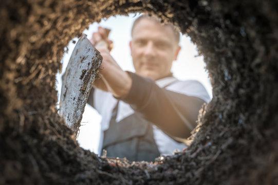 Gärtner gräbt mit einem Spaten ein Loch zum Anpflanzen von Pflanzen