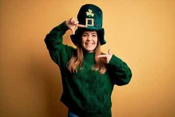 Young beautiful brunette woman wearing green hat on st patricks day celebration smiling making...