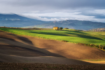Amazing spring landscape with green rolling hills and farm houses in the heart of Tuscany in morning