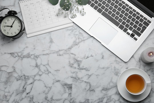 Flat lay composition with laptop and cup of tea on white marble table. Space for text