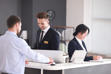 Receptionists working with visitor in office