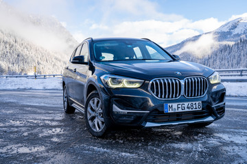Brand new black BMW X1 SUV 2020 parked in Switzerland by the highway with beautiful winter mountains in the background.