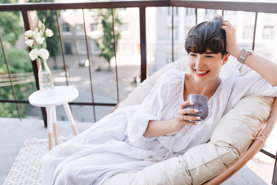 Attractive girl in white summer dress lying on sofa on terrace with cup of coffee and laughing. Portrait of joyful brunette woman wears trendy accessories looking away with smile on blur background.