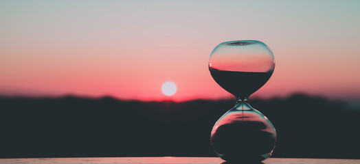 Hour glass against the background of the rising sun and the pink sky, art photography