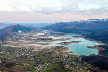 Aerial view of beautiful green lake and islands surrounded by mountains. Autumn landscape at evening. Large artificially formed lake at evening. Ramsko lake, Bosnia and Herzegovina.