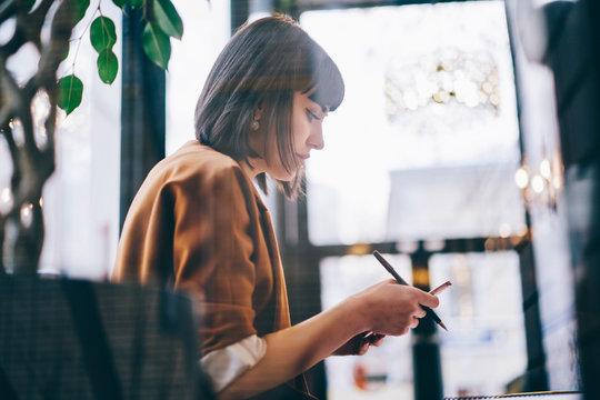 Stylish female using smartphone in cafe