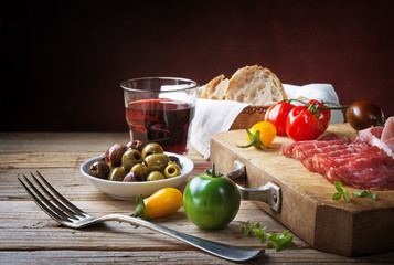Rustic snack: salami, olives, tomatoes and red wine