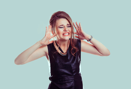 Too loud. Closeup portrait stressed woman covers ears with hands yelling screaming with temper tantrum isolated light green wall background. Negative human emotion facial expression feeling reaction