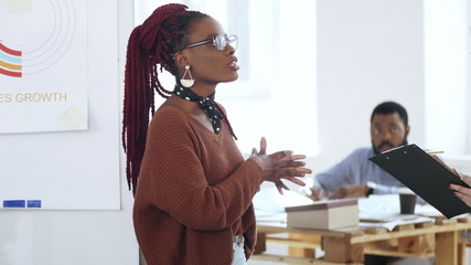 Happy young casual African woman boss in eyeglasses leading discussion, chatting to colleagues at modern light office.