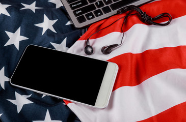 American flag waving with modern smartphone with blank screen, black headphones