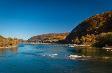 The Potomac River in Harper's Ferry, West Virginia, on a sunny Day with colorful Foliage on Trees