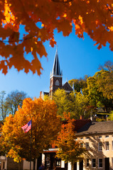 The Main Street of Harpers Ferry in West Virginia, USA, with St. Peter's Church Steeple on a sunny Day in Fall with blue Sky and colorful Foliage on Trees