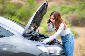 Asian young unhappy woman talking on a cell phone  in front of the open hood  broken down car On Country Road Phoning For Help. Broken Car On The Road in During journey..