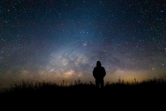 Silhouette man looking milky way in summer night sky