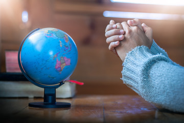 Close up hands praying for globe on wooden table, christian concept.