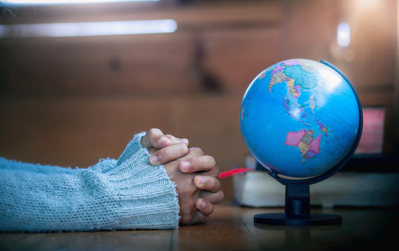 Close up hands of young christian praying for globe, for stop Disease Virus and War in the world, christian concept.