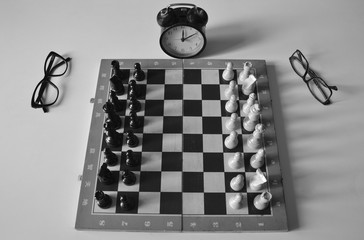 Black and white picture of old flawed hessboard with pieces. The glasses are on the sides, shabby dusty alarm clock shows time.