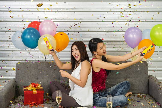 Two young asian girls siting on sofa with many color balloons popping shooting confetti.