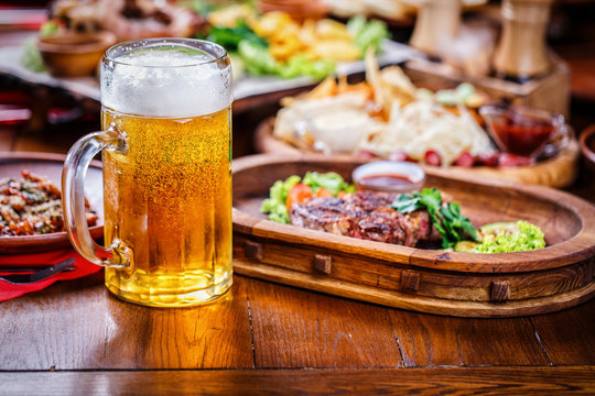 A glass of light beer on the background of a table with snacks.