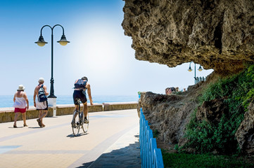 Cyclist and people walking on the promenade of Torremolinos, Malaga, Spain Wall mural