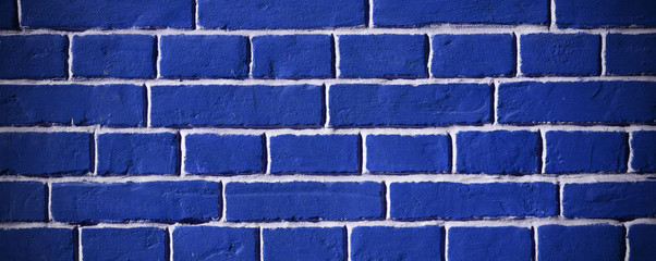 Brick wall of Classic Blue Color. Facade of the building with new plaster. Abstract banner. Brickwork. Background. Texture. Banner.
