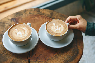 Two cups of aromatic coffee cappuccino or latte on a wooden table. person holds a cup with hand. Concept of meeting or relaxing. Tasty morning drinks.