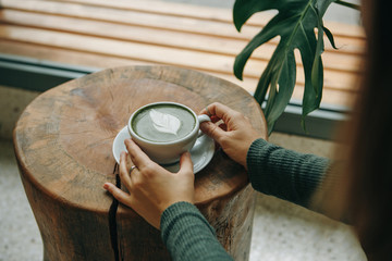 Girl drinks aromatic fresh and healthy green matcha latte tea in a cafe.
