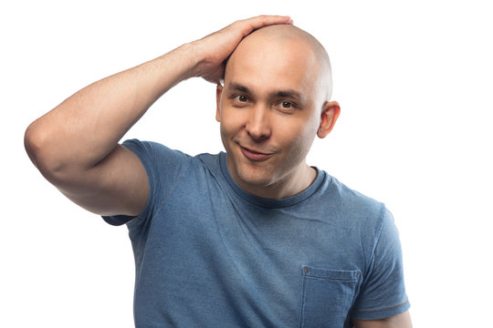 Portrait of happy bald man touching shaved head