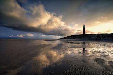 dramatic clouds over lighthouse on sea coast