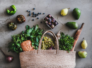 Flat-lay of healthy grocery shopping eco-friendly bag with fresh vegetables, fruit, greens, herbs, bread and sausage over concrete background, top view. Local farmers market concept
