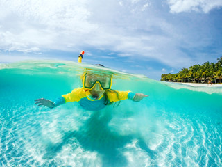 Split underwater photo of child in mask snorkeling in blue ocean water near tropical island